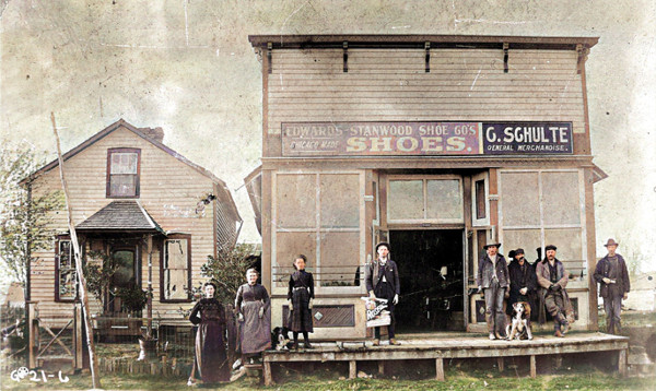 Latter 1800s people posed in front of G Schulte General Merchandise Store, colorized image
