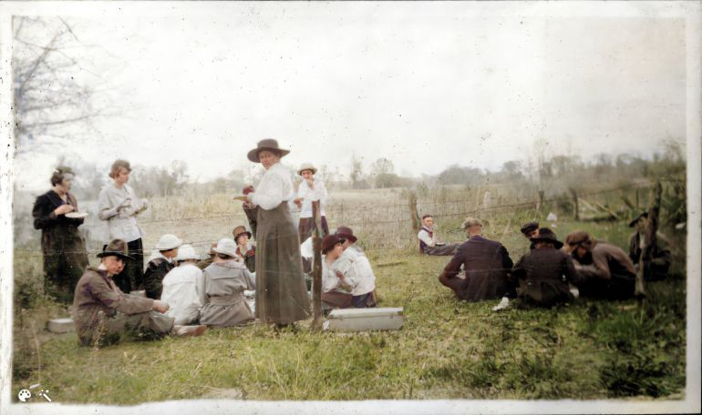 Women and men eating, seated or standing on the grass near a pasture's barbed wire fence, wearing 1918 attire, hats.